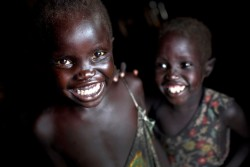 On 21 October 2016, two children smile together at their temporary home in the  UN Protection of Civilian Camp (POC) Bentiu, South Sudan. Thousands of people have fled Leer in recent weeks as fighting intensifies between rebel and government soldiers and have arrived the POC that is protected by the UN Mission to South Sudan (UNMISS) that is now home to 105,000 people.