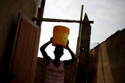 水に入ったバケツを運ぶ13歳の女の子(2016年2月撮影)