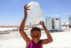 ラッカから50kmにある難民キャンプで、頭から水をかける男の子 (シリア、アイン・イッサ)2017年6月3日撮影
