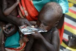 ユニセフが支援する外来治療センターで、すぐに食べられる栄養治療食(RUTF)を食べる子ども(南スーダン)