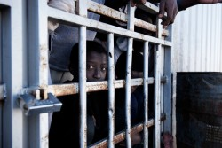 "A migrant looks out from behind the bars of a cell at a detention centre in Libya, Tuesday 31 January 2017. The detention centre was constructed in 2006 following an agreement between the Italian and Libyan governments in an attempt to stem the flow of migrants reaching Italy. When UNICEF visited the centre on 31 January 2017, the population consisted of 27 women (four of whom were pregnant), one 11-month old child, a four year old, as well as 1,352 men - of which 250 were under the age of 16. The centre is at the crossroads of areas controlled by different militias fighting with each other. For this reason it is a very dangerous centre, for officers who work there and for migrants in detention. The detention centre is currently managed by the Libyan National Army, and most migrants remain there for a period of 8 to 10 months according to the manager Abdalhamad Altunisa. ""Children are often alone, they cross 2000 kilometres of desert without their families, and they are rescued at sea without documents"", said Altunisia ""this makes it difficult for us to know their real nationality and age. Before 2014 we brought them back to the border between Nigeria and Libya to take them back to their countries, but after the last civil war it was much more difficult. Those areas are dangerous even for us"". Migrants who were being held in the cells said they are rarely allowed out. Many of the those being held are sick, and some detainees are said to have passed away because they have no access to medical care. The director of the centre, Altunisa, said ""the official government [of Sarraj] does not give us the money to pay salaries and to pay those who bring us food. So often we do not have enough food or drinking water. This winter was particularly cold and in recent weeks 15 migrants froze to death."" Libya is a country in turmoil. Since 2014 security is precarious, living is hard, and violence is commonplace. The country is riven with militias in conflict with each oth"