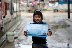 海水淡水化の工程が書いてある冊子を持つ男の子。
