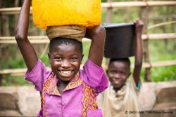 ユニセフの支援を受けて建設された水汲み場から、水を運ぶ子どもたち