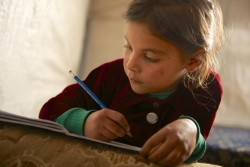 "On 7 December 2013 in Lebanon, Aliya, 7, completes homework in the tent she shares with 16 family members, in an informal tented settlement for Syrian refugees in Dalhamieh, a small village in the Bekaa Valley. Aliya and her brother Ali are the youngest children of a large family, spanning her father's three marriages. Most of her siblings fled from their village in Idlib Governorate two years earlier, while Aliya and Ali remained with their parents in Lebanon. The area where they lived was regularly affected by violence. ""There were many missiles and rockets,"" Aliya recalled. ""Every day they would fall on us. I was afraid. My brother and I would go hide in my room."" About one year ago, their home was shelled in an attack that killed their mother and father. Neighbours then called the children's oldest brother, Abu-Thamer, to return to the Syrian Arab Republic for his siblings. ""Ali did not speak at all until we got to Lebanon,"" he said. The transition to life away from home has also been difficult for Aliya. ""I was surprised when I first saw the tent here, I thought, 'My God, how can everyone stand this?' … but when I thought of the bombing back home, I said to myself that this is better."" Aliya had been attending a tented school, but it was recently closed due to inclement weather. ""The tent … does not keep water out. It was closed so we don't get sick. They didn't tell us when it will open again, but I want it to because I want to learn."" As the Syrian crisis enters its fourth year, needs are escalating at an increasingly urgent pace, with children bearing the greatest toll. Since March 2011, over 7,000 children have lost their lives in the violence, while hundreds of thousands have been wounded, some of whom must now live with life-long disabilities caused by their injuries. By mid-December 2013, the conflict had left 6.5 million people displaced internally. They are among 9.3 million people inside the country in need of hu"
