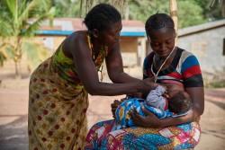 生後3カ月の息子に授乳する母親のカマラさん(写真右)。カマラさんの母親(写真左)が、寄り添って手助けをしている。(シエラレオネ)