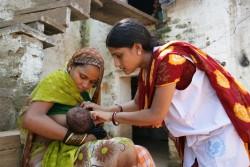 20歳の母親バビタさんが、生後15日の新生児に授乳している。ユニセフのカウンセラー(写真右)は、各家庭をまわり、正しい母乳育児の方法について伝えている。(インド)