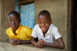 (left) Bakarr Sow, 14, and Sallu Ansumana, 12, stand outside their home in in the village of Gondama, Bo District, Sierra Leone, Saturday 3 June 2017.  Sierra Leone is one of seven countries in sub-Saharan Africa where more than a quarter of the population is infected with malaria at any one time, according to World Malaria Report (World Health Organization 2016), with nearly three in ten Sierra Leoneans suffering from the disease. Malaria contributes to an estimated twenty per cent of child mortality, and is the cause of nearly four in ten hospital consultations country-wide. Pregnant women are at particular risk from malaria, which contributes to high rates of miscarriage, pre-mature births and low birth weights. Four in ten children aged 6-59 months tested positive for malaria (via microscopy), according to survey data in the just published Sierra Leone Malaria Indicator Survey (2016). As stated in the Sierra Leone National Strategic Plan 2016-2020, all children under 5 and all pregnant women should sleep under a treated mosquito net every night to prevent malaria complications.   Between 1 to 10 June 2017, the National Malaria Control Program of the Ministry of Health and Sanitation distributed around 4.3 million insecticide treated mosquito bed nets in a nationwide mass distribution campaign. The campaign was funded by the UK Department for International Development (DfID) and the Global Fund to Fight AIDS, TB and Malaria, through UNICEF. The mass distribution drive also saw the distribution of vitamin A supplements for children aged 6-59 months and Albendazole deworming tablets for children aged 12-59 months.