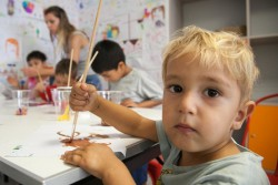On 17 August 2016 in the Blue Dot Family Center, Athens, Greece, a child paints.  In this UNICEF supported centre, run by Faros, services for migrants and refugees include showers, mother-baby feeding corners with breastfeeding support, child-friendly space and play area, wifi, legal referral, medical referral, and counselling.  The centre supports between 100-150 mothers and children each day, including those who travel in from camps outside Athens and many refugees and migrants from the neighbourhood near Victoria Square.  With the sudden increase of arrivals, hundreds more refugee and migrant children are becoming stranded in Greece with critical needs such as education and protection, says UNICEF. More people arrived in the first three weeks of August than all of July 2016 (1,920 for July; 2,289 as of 24 August). This new influx comes at a time when Greece is struggling to cope with a strained welfare system due to the ongoing economic crisis, leaving refugee and migrant children facing a double crisis. In total, children make up nearly 40 per cent of the current stranded population.  Getting children into education is a key priority for UNICEF and its partners in Greece, especially in the light of recent reports of children at risk. UNICEF has been supporting learning and recreational activities for refugee children in Skaramangas camp, near Athens, with the Greek NGO Piraeus Open School for Immigrants, as well as providing 11 container classrooms. UNICEF education programmes are being scaled up beyond Attica to other camps, targeting at least 5,000 children by the end of the year and working with the Ministry of Education to help integrate refugee children into the Greek education system.