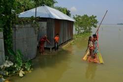 バナナの木で作ったボートで、シェルターまで移動する子どもたち。 (バングラデシュ・クリグラム県)2017年8月17日撮影