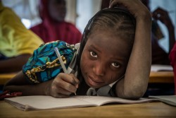 "On 17 February, a girl looks up from writing during a class, in a temporary learning space in the Ngagam displacement camp in the Diffa region. In late February 2017, UNICEF Goodwill Ambassador Orlando Bloom travelled to Diffa, south-east Niger, to highlight the ongoing humanitarian crisis in West Africa's Lake Chad Basin (Niger, Nigeria, Chad, Cameroon). Boko Haram violence has caused huge population displacements, leaving hundreds of thousands of children in a critical situation, out of education and at risk of malnutrition. Across the four countries, 2.3 million people are now displaced, making this one of the fastest growing displacement crises in Africa. The Diffa region currently hosts over 240,000 internally displaced people, refugees and returnees—including 160,000 children. UNICEF is providing safe environments for children in Niger and across the region to play, as well as helping them return to school, and training teachers to identify and support children traumatised by the increasing violence in the region. UNICEF is also providing lifesaving treatment for children suffering from severe malnutrition. ""This visit has been extremely moving. Every single child I met is affected by this conflict and in desperate need of basic services such as clean water, psychological care and education to help them recover from the atrocities they have suffered and witnessed. They deserve a childhood,"" said Bloom. UNICEF and its partners in Nigeria, Cameroon, Chad and Niger have increased the level of assistance to thousands of families in the region, with access to safe water, education, counselling and psychosocial support, as well as vaccines and treatment for malnutrition. However, a shortage of funding and difficult access due to insecurity have hindered the delivery of humanitarian assistance to thousands of children in need."