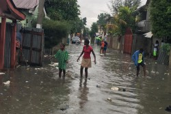 ハリケーン「イルマ」が近づく中、水没した道を歩く女性と子どもたち。(ハイチ)2017年9月7日撮影