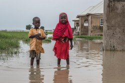 Children stand in a pool of water in Bakassi IDP camp in Maiduguri, Borno State, Nigeria, Tuesday 1 August 2017. The rainy season, which begins in June and generally lasts three to four months, brings heavy rain and flooding to camps hosting internally displaced persons across northeast Nigeria, where as of June 2017, 1.82 million people have been displaced from their homes by the Boko Haram insurgency. Some 56% of the displaced are children, who are particularly affected when floods impact WASH systems. To mitigate against the rainy season, flood vulnerability mapping was carried out in IDP camps in Borno state. An estimated 59 IDP camps (out of 164) were deemed at risk of flooding, potentially affecting 70,5862 households (328,000 persons), including 66,000 children under the age of five. To address these issues, the shelter and camp coordination sector worked on drainage issues in camps and UNICEF positioned dewatering pumps to sites with high risk of water-logging.