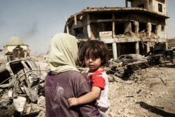 A woman carries her child through the debris of buildings and vehicles destroyed during intense fighting as they flee the Old City for safe areas in Mosul, Iraq, Thursday 6 July 2017. Partially visible at left is the destroyed Great Mosque of al-Nuri. The end of the violence in Mosul in July 2017 is likely to be a turning point for Iraq, but it will not bring the guns to silence as the battle will soon turn to Tal Afar, West Anbar and Hawija. Three years of traumatic experiences and months of intense fighting have left children and families in Mosul struggling with the physical and psychological wounds of war, with childhoods turned into nightmares of brutality, displacement and loss. Many are being treated in trauma centres in west Mosul with bullet and shrapnel wounds are children and many children who fled the intense fighting between government and non-government actors are severely distressed and need psychosocial care. Warring parties actively recruited children into the fighting, depriving them of a normal childhood and the chance of a better future.Some children are being held in detention centres. UNICEF is providing these children with legal representation, education, psychosocial assistance, vocational training, and helping to improve the conditions of the facilities where children are held. Providing schools, water, sanitation and health services will be crucial for all Iraqi children and their families to return home. Otherwise, the risk is not only of a lost generation, but also severely restricted opportunities to build a solid foundation for coexistence, tolerance and peace in the future.