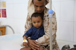 A child suffering from cholera is held by his father as he receives treatment at the Alsadaqah Hospital, Aden, Yemen, Monday 14 August 2017. The world's worst acute outbreak of acute watery diarrhea and cholera continues spreading in Yemen. Between late-April and July 2017, 436,625 suspected cases and 1,915 deaths had been reported in 21 of 22 governorates. Health, water and sanitation systems are struggling to function as a result of the ongoing conflict, and lack of regular salary payments for many public sector workers have created the ideal conditions for the disease to spread. As part of efforts to halt the spread of AWD/cholera, UNICEF and its partners are reaching out to communities through a nationwide awareness campaign. Across Yemen, thousands of volunteers are going from house to house to raise awareness and provide advice to families on how they can best protect themselves from the potentially fatal infection. The teams provide 15 to 20 minutes of counselling, followed by demonstrations on how to properly wash hands with soap before eating food or after going to the bathroom. They also stress the importance of boiling water before drinking. The campaign is expected to reach 3.5 million families across the country.