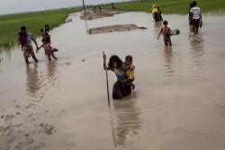 安全を求めてミャンマーからバングラデシュへ逃れてきたロヒンギャ難民の少女と子ども。国境を越えた後、安全な避難場所を求めて、洪水地域や水田を歩いている。