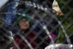 難民・移民のための仮設キャンプにて、フェンスの側に立つ子ども。(ギリシャ)2016年2月撮影
