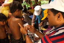 保健員から、予防接種を受ける子ども。