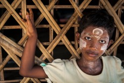 A young Muslim girl stands outside a shelter at the Sin Tet Maw camp for internally displaced persons in Rakhine State, Myanmar, Thursday 6 April 2017.  In 2017, working with the Government of Myanmar, UNICEF will strive to meet the basic needs of the most vulnerable internally displaced children. Myanmar is experiencing three protracted humanitarian crises, each with its own set of complex underlying factors. In Rakhine State, inter-communal violence that erupted in 2012 continues to plague 120,000 internally displaced people spread across 40 camps or informal sites, as well as host communities. Eighty per cent of the displaced are women and children. In Kachin State, armed conflict that reignited in 2011 continues to impact communities caught in the crossfire between an ethnic armed group and the Myanmar army. Nearly 87,000 people remain displaced as a result, including 40 per cent who are in areas outside of government control. An additional 11,000 people remain displaced in northern Shan State, where a similar conflict broke out in 2011. Compounding the protracted crises are issues related to religious and/or ethnic discrimination, exploitation, chronic poverty, vulnerability to natural disasters, statelessness, trafficking and humanitarian access. In addition to the humanitarian crises in Rakhine, Kachin and Shan states, Myanmar is impacted by humanitarian situations in other parts of the country, including natural disasters, health emergencies and small-scale displacements.