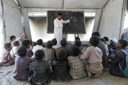Students listen to their teacher during a class held in a UNICEF tent school, after  the Aal Okab school which they used to attend was destroyed in June 2015, in Saada, Saada Governorate, Yemen, Monday 24 April 2017. Since the start of 2017, the humanitarian situation in Yemen has substantially deteriorated. According to analysis by the Humanitarian Country Team released in April 2017, the number of people in need of assistance and protection is 20.7 million. Increasing tensions and hostilities in the western coast since January have left over 50,000 people displaced, many of them in locations where humanitarian access has been extremely challenging. Concerns regarding the continuity of operations of the Al Hudaydah port persist and the potential closure of the main port in Yemen would have significant consequences for the humanitarian operation. Between April and July 2017, 400,000 cases of suspected cholera and nearly 1900 associated deaths were recorded. Vital health, water and sanitation facilities have been crippled by more than two years of hostilities, and created the ideal conditions for diseases to spread. Nearly 2 million Yemeni children are acutely malnourished, which makes them more susceptible to cholera. Vital infrastructure, such as health and water facilities, have been damaged or destroyed by the conflict. Adding to the pressure on health services, more than 30,000 health workers have not been paid their salaries in more than 10 months. Yemen's education system is also on the brink of collapse, and more than 5 million children risk being deprived of their right to education. As at June 2017, over 193,000 teachers have not received their salaries during the past nine months. Moreover, school infrastructure has been affected, with 222 incidents of attacks on schools documented and verified by the Country Task Force on Monitoring and Reporting of Grave Child Rights Violations (CTF MR) between March 2015 and June 2017. At least 1,279 schools are