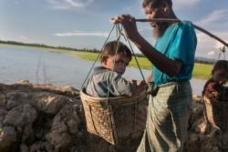 小さな男の子2人をかご入れて運び、ミャンマーから逃れてきた家族。(2017年9月93日撮影)