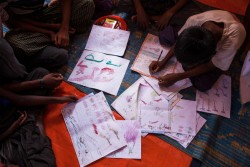 On 29 September 2017, Rohingya children draw at the children friendly space at the Balukhali makeshift refugee camp in Cox's Bazar district in Bangladesh.  A quarter of a million Rohingya children have fled Myanmar since the latest outbreak of violence began a month ago.Many more continue to cross the border into Bangladesh every day. Many are alone, have nothing and some have a hard time speaking about what they've seen. Instead, they draw pictures to help cope with the horrific scenes they've experienced and witnessed. UNICEF announced 30 September 2017 that it is planning to establish more than 1,300 new learning centres for Rohingya children who have fled Myanmar to neighbouring Bangladesh. UNICEF is currently running 182 learning centres in Rohingya camps and makeshift settlements in Cox's Bazar, and has enrolled 15,000 children. It plans to increase the number of learning centres to 1,500, to reach 200,000 children over the next year. The learning centres provide early education to children aged 4 to 6, as well as non-formal basic education to children from ages 6 to 14. In each learning centre there are three shifts, with each shift comprising of 35 children. Children learn English, Math, Burmese, Science, Arts and Anthems in the learning centres. Children also receive psychosocial counselling, and are taught hygiene and life skills.  The children are given books, pens, colouring pencils, school bags and other educational materials. Over a quarter of a million Rohingya children have fled Myanmar into Cox's Bazar since August 25.