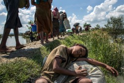 On 17 October 2017, a 10 year-old boy lies sleeping on the edge of a rice paddy as others move toward the village of Palong Khali in Bangladesh. Between 10000 and 15000 newly arrived Rohingya refugees fleeing Myanmar crossed into Bangladesh, and are stuck in Palong Khali in Cox's Bazar district approximately 2 kms from the border with Myanmar. Thousands of people are queuing up on pedestrian road in the midst of paddy fields and waterbodies in a queue approximately 1 km long. Thousands among them are children. People making long journeys by walking and crossing the river are in desperate condition. They are exhausted, dehydrated, hungry and are urgently in need of water. People are getting sick due to dehydration, while lots are also traumatized. Some children have been separated from their families during their journey.  UNICEF has mobilized resources for the newly arrived Rohingyas. Two water trucks carrying 6000 litres of water and 2000 jerrycans are on the site for distribution. Distribution started this morning by boat to the refugees located near the border area. Another 20,000 bottles of water each containing 1.5 litre are on the way from Chittagong. UNICEF is prepositioning two mobile child friendly spaces at the site for assessment and family tracing and reunification. UNICEF also plans to mobilize immunization and nutrition screening for this new influx. Two UNICEF nutrition and health teams are currently on the ground. As of 15 October 2017, at least 795,000 Rohingyas are estimated to be sheltering in Bangladesh, having fled violence and persecution in Myanmar. Violence which began on 25 August has triggered a massive and swift refugee influx across the border - an estimated 582,000 people have arrived. These refugees have joined some 213,000 people who were already in Bangladesh following earlier waves of displacement.  The Rohingya population in Cox's Bazar is highly vulnerable, many having experienced severe trauma, and are now living in extreme