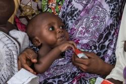 すぐに食べられる栄養治療食(RUTF)を食べる男の子。(マイドゥグリ)2017年7月撮影