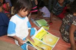 地域幼稚園で絵本を読む子ども。