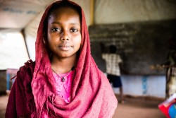 "Faozea Mahmout, 14, who attends grade CE2, stands in a classroom at the school she attends in Danamadja, southern Chad, Tuesday 13 June 2017. ""I've been going to school since the age of 6. When I left the Central African Republic, I didn't go back to school for a year and it was hard for me"" says Faozea. ""It's hard for a girl to go to school because we also have to take care of the house, so we finish our day and we are exhausted. The dignity kits helped me to keep my clothes clean for when I go to school. Before it was hard for me to come to school when I had my periods, I was not comfortable. It's important for me to stay in school so that I can become a teacher. When I went back home with the dignity kit, the girls from my neighbourhood who quit school where envious, they wanted to go back to school to have the same things.""  Since the outburst of violence in the Central African Republic in 2013, 60,000 returnees from the Central African Republic have sought refuge in southern Chad. Among them are the 17,000 people living in Danamadja refugee camp, where children are now accessing education. Yet girls face many hurdles in attending school, including a lack of basic hygiene supplies, such as sanitary pads, which can tip the balance and lead them to drop out of school.  In 2017, thanks to the Central Emergency Response Fund (CERF), UNICEF was able to distribute ""dignity kits"" to school girls living in refugee camps and returnees sites in southern Chad. The kits include soap, bleach, water buckets, and sanitary pads to helping them to pursue their education in the best conditions possible."