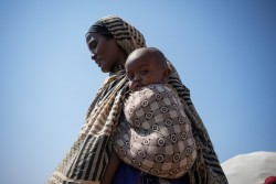 A mother carries her baby in the ADC4 internally displaced persons camp in Baidoa, Somalia, Monday 3 April 2017.  As of April 2017, the humanitarian situation in Somalia continues to deteriorate due to the severe drought, which started in the north in 2016 and is now affecting most of the country. Over 6.2 million people are facing acute food insecurity and 4.5 million people are estimated to be in need of water, sanitation and hygiene (WASH) assistance. The situation is especially grave for children. Close to one million children (under five) will be acutely malnourished in 2017, including 185,000 severely malnourished, which may increase to over 270,000 if famine is not averted. Severely malnourished children are nine times more likely to die of killer diseases like cholera / acute watery diarrhea and measles, which are spreading.   The drought is also uprooting people, with more than 530,000 displaced since November 2016, adding to the 1.1 million already internally displaced (IDPs). This includes 278,000 new IDPs in the month of March alone, with 72,000 new arrivals in Mogadishu and 70,000 in Baidoa. In addition, the number of people crossing into Kenya is increasing. The rapid scale of displacement increases the risk of family separation and gender-based violence. Children are also dropping out of school, with 50,000 children reported to have stopped going to school, and an additional 40,000 at risk of being forced to interrupt their schooling.  The Gu (April-June) rains are slowly unfolding, bringing much needed relief to parts of the country. But the rains also spell danger for children. If they come in full they will inflict further misery on children living in flimsy, makeshift shelters made of twigs and cloth or tarps. If the Gu rains fail, and if assistance doesn't reach families, more people will be forced off their land into displacement camps. Outbreaks of malaria are already imminent, as is an upsurge of cholera.  The drought has also forced some