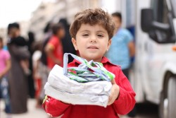 "A child carries nutritional supplements which he received after being examined by health workers at a mobile health clinic in the Al-Hilwanieh neighbourhood of eastern Aleppo, Syrian Arab Republic, Wednesday 14 June 2017. With no functioning public health centers in eastern Aleppo as of July 2017 and little cash among families who are returning to pay for private healthcare, UNICEF-supported mobile health clinics provide essential primary health services free of charge. Every day at nine in the morning, 25 health workers in seven trucks start their journey through the streets of east Aleppo. In order to reach as many people as possible, the trucks park close to crowded bread distribution points. The seven clinics-on-wheels treat more than 400 children and women every day for common illnesses, providing medicine and immunization services, as well as micronutrients and nutritional supplements to treat and prevent malnutrition.  ""The most common cases we see are related to malnutrition, diarrhoea and water-borne diseases,"" says Dr. Kamal who works in one of the UNICEF-supported mobile clinics. ""Living amidst the rubble, combined with a general lack of safe water, means hygiene conditions in the area have worsened, causing more children to fall ill,"" he added. As more people return to the area, there is increasing demand for health services. ""Although we come here every day for 6 hours, we barely stop work for one minute. We see one child or mother every 10 minutes while dozens of others are lining up outside in the scorching heat,"" said Siba, a nurse at one of the clinics. To help prevent malnutrition, a team of community volunteers also accompanies the mobile health clinic, passing on information to mothers and answering questions on how to provide more nutritious diets for their young children. ""During one-on-one sessions with mothers, we hear all kinds of dreadful stories. Many women have lost their husbands and are facing the world alone,"" s"