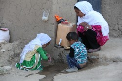 "(Right) Mercia, 20, checks that her daughter Sohila, 5, (left) and son Alisina, 3, wash their hands properly outside their home in Chaw village, Nili district, Daikundi province, Afghanistan, Wednesday 1 November 2017. ""The toilet was there but it wasn't always used. This initiative helped us to realise that we should use it and to keep some soap nearby,"" says Mercia. The district of Nili, in Daykundi province, central Afghanistan, was declared as the country's first 'open defecation free district' at a ceremony on 1 November 2017. Towns and villages across Nili took on the 'Community-led Total Sanitation' approach in which families identify areas around their homes that are used as toilets. Through a combination of shock, shame, pride and disgust, families without a toilet decide to build their latrine. Community-wide commitment and some peer pressure does the rest and typically after three to six months an entire community has given up defecating in the open, contributing to a healthier environment for everyone.  The risks associated with diarrhoeal infections are exacerbated in Afghanistan – a country where some 1.2 million children are already malnourished and 41 per cent of children are stunted. Poor sanitation and hygiene compound malnutrition, leaving children more susceptible to infections that cause diarrhoea, which in turn worsens malnutrition.  In 2017, UNICEF in Afghanistan has already supported more than 500 Afghan communities to be declared and certified as open defecation free. Global research has shown that in some communities where people now use toilets rather than fields or other outside areas, stunting has been reduced by 23 per cent. Reducing cases of diarrhoea also cuts down on significant health costs that families face when having to treat their children for regular sickness."