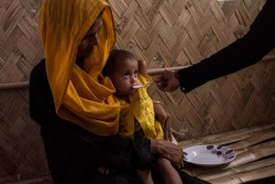 A mother receives nutritional advice as her child is fed at a newly opened UNICEF-supported nutrition centre in a remote part of the Uchiprang refugee camp, near Cox's Bazar, Bangladesh, Saturday 21 October 2017. As at 20 October 2017, well over half a million Rohingya people have crossed into Bangladesh's southern district of Cox's Bazaar since late August after escaping horrific violence in neighbouring Myanmar. They have joined some 200,000 others who came in earlier refugee influxes. Almost 60 per cent of the latest arrivals are children, crossing at a rate of between 1,200 and 1,800 per day.  High levels of severe acute malnutrition among young children have been found in the camps, and antenatal services to mothers and babies are lacking. Support for children traumatised by violence also needs to be expanded. Expanding the provision of safe water, sanitation and improved hygiene for Rohingya children is the top priority, amid concerns over a possible outbreak of diarrhea and other waterborne diseases. Most Rohingya children are not fully immunized against diseases such as measles. UNICEF is also focused on providing Rohingya children with learning and support services in child-friendly spaces, and working with our partners to address gender-based violence. UNICEF is calling for an end to the atrocities targeting civilians in Myanmar's Rakhine State, and for humanitarian actors to be given immediate and unfettered access to all children affected by the violence there.  At present, UNICEF has no access to Rohingya children in Northern Rakhine State. At the end of September 2017, UNICEF announced that it is planning to establish more than 1,300 new learning centres for Rohingya children who have fled Myanmar to neighbouring Bangladesh. UNICEF is running 182 learning centres in Rohingya camps and makeshift settlements in Cox's Bazar, and has enrolled 15,000 children. It plans to increase the number of learning centres to 1,500, to reach 200,000 children