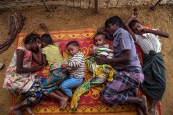 (Left) Morjina Khatun, 12, and her sister Mobina Khaun, 7, along with her other siblings demonstrate how they sleep on a mat placed on the ground at their shelter in Balukhali makeshift settlement, Cox's Bazar, Bangladesh, Sunday 29 October 2017. During the brief demonstration, three of the children fell asleep in the afternoon heat. As of 5 November 2017, the humanitarian situation for Rohingya refugees in Bangladesh remains dire, with some 607,000 newly arrived refugees since 25 August 2017.  According to the Inter-Sector Coordination Group rapid needs assessment, 58 per cent of new arrivals are children and 60 per cent are women including a high number of pregnant (3 per cent) and lactating women (7 per cent). With the new influx, the current total number of Rohingya who have fled from Myanmar into Bangladesh, coupled with the affected population in the communities, has reached a staggering 1.2 million. There are 720,000 children among the new arrivals, existing Rohingya populations and vulnerable host communities who are affected and need urgent humanitarian assistance including critical life-saving interventions. Sultan Ahmad, 15, and his five siblings are Rohingya refugees from Andamg village in Mongdo, Myanmar. The children's father was imprisoned in Myanmar, according to Sultan, after government forces searching for suspected ISIS members swept through their village. Their mother died as the family made the ten day journey by foot to Bangladesh. Despite arriving at the settlement two months ago with their aunt and uncle, Sultan has yet to register for food aid. As the eldest child, Sultan now cares for his five siblings with whom he lives in a shelter adjacent to his aunt and uncle.