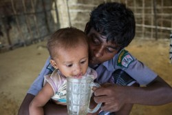 Sultan Ahmad, 15, gives his brother Osman Goni, 1.5, water at their shelter in Balukhali makeshift settlement, Cox's Bazar, Bangladesh, Sunday 29 October 2017. As of 5 November 2017, the humanitarian situation for Rohingya refugees in Bangladesh remains dire, with some 607,000 newly arrived refugees since 25 August 2017.  According to the Inter-Sector Coordination Group rapid needs assessment, 58 per cent of new arrivals are children and 60 per cent are women including a high number of pregnant (3 per cent) and lactating women (7 per cent). With the new influx, the current total number of Rohingya who have fled from Myanmar into Bangladesh, coupled with the affected population in the communities, has reached a staggering 1.2 million. There are 720,000 children among the new arrivals, existing Rohingya populations and vulnerable host communities who are affected and need urgent humanitarian assistance including critical life-saving interventions. Sultan Ahmad, 15, and his five siblings are Rohingya refugees from Andamg village in Mongdo, Myanmar. The children's father was imprisoned in Myanmar, according to Sultan, after government forces searching for suspected ISIS members swept through their village. Their mother died as the family made the ten day journey by foot to Bangladesh. Despite arriving at the settlement two months ago with their aunt and uncle, Sultan has yet to register for food aid. As the eldest child, Sultan now cares for his five siblings with whom he lives in a shelter adjacent to his aunt and uncle.
