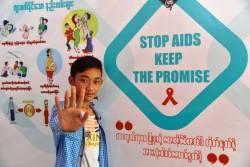 エイズ啓発ポスターの前でポーズをとる男の子。(ミャンマー)2017年4月撮影