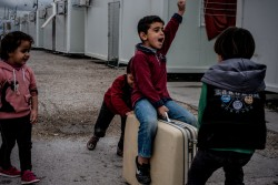 難民キャンプのごみ捨て場で見つけたスーツケースで遊ぶ子どもたち。(ギリシャ)2017年3月撮影
