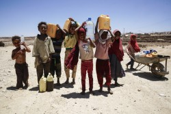 Children carry water containers in the Khamir IDP settlement, Amran Governorate, Yemen, Friday 14 April 2017. The landowners on which the IDP settlement is located recently turned off the main water supply, meaning residents have to walk long distances to fetch water. Since the start of 2017, the humanitarian situation in Yemen has substantially deteriorated. According to analysis by the Humanitarian Country Team released in April 2017, the number of people in need of assistance and protection is 20.7 million. Increasing tensions and hostilities in the western coast since January have left over 50,000 people displaced, many of them in locations where humanitarian access has been extremely challenging. Concerns regarding the continuity of operations of the Al Hudaydah port persist and the potential closure of the main port in Yemen would have significant consequences for the humanitarian operation. Between April and July 2017, 400,000 cases of suspected cholera and nearly 1900 associated deaths were recorded. Vital health, water and sanitation facilities have been crippled by more than two years of hostilities, and created the ideal conditions for diseases to spread. Nearly 2 million Yemeni children are acutely malnourished, which makes them more susceptible to cholera. Vital infrastructure, such as health and water facilities, have been damaged or destroyed by the conflict. Adding to the pressure on health services, more than 30,000 health workers have not been paid their salaries in more than 10 months. Yemen's education system is also on the brink of collapse, and more than 5 million children risk being deprived of their right to education. As at June 2017, over 193,000 teachers have not received their salaries during the past nine months. Moreover, school infrastructure has been affected, with 222 incidents of attacks on schools documented and verified by the Country Task Force on Monitoring and Reporting of Grave Child Rights Violations (CTF MR) between M