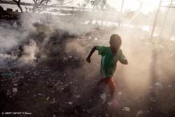 ごみを燃やす煙の中を走る男の子。(マリ)2012年12月撮影