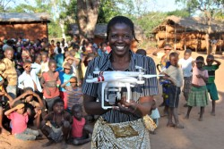 "Resident Rhoda Nkhambule holds a drone following a public demonstration of the technology to residents in Thipa vllage, Kasungu District, Malawi, Thursday 29 June 2017. ""I know how important vaccinations are to our children,"" says Rhoda, ""Medical staff tell us that children have to receive their vaccination on time, but our children can only receive vaccinations once a month because we are so far from the health centre. If they miss it, they have to wait for the following month, putting them at risk of catching diseases."" Thipa village is 19 kilometres from the nearest health centre in Dwangwa and the only way to get there is either by bicycle or walking for four hours. On 29 June 2017, the Government of Malawi and UNICEF launch an air corridor to test potential humanitarian use of Unmanned Aerial Vehicles (UAVs), also known as drones. The corridor is the first of its kind in Africa and one of the first globally with a focus on humanitarian and development use. It is centred on Kasungu Aerodrome, in central Malawi, with a 40 kilometre radius (80 kilometre diameter) and is designed to provide a controlled platform for the private sector, universities and other partners to explore how UAVs can be used to help deliver services that benefit communities. The UAV corridor will run for at least one year, until June 2018. Since the announcement in December 2016, 12 companies, universities and NGOs from around the world have applied to use the corridor. These include drone manufacturers, operators and telecom companies such as GLOBHE (Sweden) in collaboration with HemoCue and UCANDRONE (Greece), and Precision (Malawi), all of which were present at the launch to demonstrate connectivity, transportation and imagery uses respectively. UAV technology is still in the early stages of development. UNICEF is working globally with a number of governments and private sector partners to explore how UAVs can be used in low income countries. All projects adhere to a strict set of inno"