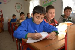 Ahmad, 9, in class at Maysaloon school, Eastern Aleppo. Ahmad is forced to work to support his family.