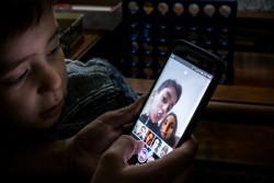 カナダで暮らすシリア難民の子どもたちが、母親のスマートフォンを使ってソーシャルメディアにアクセスしている。