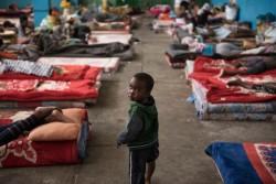 拘留施設の床に敷いたマットレスの間を歩く子ども。(リビア)2017年8月撮影
