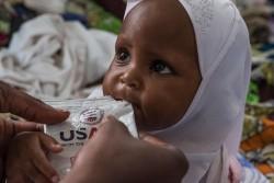 すぐに食べられる栄養治療食を食べる2歳の子ども。(2017年10月30日撮影)