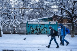 "(Foreground left) Sasha Sechevoi, 12, walks to school in the town of Avdiivka, Donetsk Oblast, Ukraine, Monday 27 November 2017. Sasha's father was unknown at birth and his mother later abandoned him, leaving him in the custody of his extended relative, Valentina.  ""There hasn't been any shelling last week. I feel like I want to live again,"" Valentina says. ""We can still hear gunfire each day, and regularly artillery fire. Sasha wouldn't mind the sounds. He would just keep riding his bicycle.""  Even as neighbours were wounded and killed in fighting, Sasha continued to play outside. In August, 2016, Sasha was riding his bicycle when a bullet shattered his ankle. His dream of becoming a professional football player may be jeopardized, worries Valentina. ""Before he got hit, Sasha was like a proper child. Now he seems like a grown up"" Valentina says, ""He's more aware, more cautious. And he can tell from the sounds what type of weapon is working; whether it's automatic rifle fire or artillery."" Because of the fighting and no heating, the local school operates three times a week, with classes cut short to 20 minute sessions. Sasha walks to school through neighbouring yards to avoid the road before boarding the bus. At school, there used to be 20 students in his class, but that number has dwindled to ten as families fled in search of safety.  The shelling has damaged infrastructure in the city, and Sasha's home is without gas or clean water. The electricity grid was damaged too, but was repaired because it is the last means of heat for residents during the winter months.  In the afternoon, shelling echos through the city. ""It's normal now,"" Valentina says, ""but you never get used to the fact that you cannot know whether you'll wake up again the next morning."" As of December 2017, the situation in eastern Ukraine remains volatile, and violence continues despite the latest ceasefire agreements committed on 19 July 2017. The live"