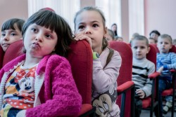 Children listen to a mine awareness class given by the Swiss Foundation for Mine Action (FSD) at school number 2 in Avdiivka, Donetsk Oblast, Ukraine, Monday 27 November 2017. The foundation, which is partially funded by UNICEF, teaches children to exercise caution around unexploded ordnance and land mines through fairytales and plays.  Conflict in Ukraine has led to thousands of rounds of unexploded ordnance being left in fields and in civilian areas. Fighting between the sides often takes place in built up towns, and military placements can be found between homes and next to schools. Children and adults are regularly injured and killed when they come upon these unexploded munitions.  Avdiivka, a city of about 20,000 people, sits right on the contact line which divides government and non-government controlled areas in eastern Ukraine and where fighting is most intense. There is daily shelling, and at some points opposing sides face off at just 300 meters, resulting in regular small-arms skirmishes.  As of December 2017, the situation in eastern Ukraine remains volatile, and violence continues despite the latest ceasefire agreements committed on 19 July 2017. The lives of children and their families, especially those living along the contact line continue to be at risk.  According to a December 2017 report by the United Nations Office for the Coordination of Humanitarian Affairs, millions of people are continuing to suffer unnecessarily due to the entrenched political impasse and the ongoing armed conflict. Despite many attempts at a ceasefire, hostilities continue with almost daily shelling, frequent localized clashes, and rapidly escalating mine and unexploded ordinance contamination. Given the restrictions on access, just under a million crossings of the contact line occur each month, with people forced to wait for many hours in long lines with minimal services. Four years on, the prolonged conflict and socioeconomic disparity between the government controlled