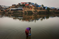 A Rohingya refugee washes items in one of the many man made dams in Balukhali makeshift settlement, Cox's Bazar, Bangladesh, Saturday 25 November 2017. The humanitarian situation for Rohingya refugees in Bangladesh remains dire. The influx of Rohingya refugees from northern parts of Myanmar's Rakhine State into Bangladesh restarted following attacks at Myanmar Border Guard Police posts on 25 August 2017 and as of 30 November 2017, the Inter-Sector Coordination Group (ISCG) reported that 646,000 Rohingya refugees have entered Bangladesh since the attacks. With the new influx, the current total number of Rohingya who have fled from Myanmar into Bangladesh, coupled with the affected population in the communities, has reached a staggering 1.2 million. There are 720,000 children among the new arrivals, existing Rohingya populations and vulnerable host communities who are affected and need urgent humanitarian assistance including critical life-saving interventions. The inter-agency Humanitarian Response Plan (HRP) for 2017-18 identified the areas of WASH, health, nutrition and food security and shelter for immediate scale-up to save lives in both settlements and host communities. As per the HRP, the Rohingya population in Cox's Bazar is highly vulnerable, many having experienced severe trauma, and are now living in extremely difficult conditions. The limited WASH facilities in the refugee established settlements, put in place by WASH sector partners including UNICEF prior to the current influx, are over-stretched, with an average of 100 people per latrine. New arrivals also have limited access to bathing facilities, especially women, and urgently require WASH supplies including soap and buckets. Given the current population density and poor sanitation and hygiene conditions, any outbreak of cholera or Acute Watery Diarrhoea (AWD), which are endemic in Bangladesh, could kill thousands of people residing in temporary settlements. Moreover, children, adolescents and