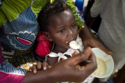 """A mother is feeding her child with """"4-star porridge""""  during a cooking demonstration session organized by a UNICEF partner in Bumbu, a district of Kinshasa, capital of the Democratic Republic of Congo, on October 20th, 2017."""