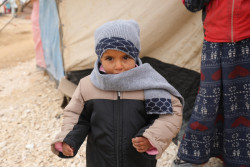 """I feel warm"" says 5-year-old Khalid, who with his 3 siblings received winter clothes during UNICEF-supported winter response in Areesheh make-shift camp.  Husain and his family of 5 fled from Deir-ez-Zor 3 months ago because of fighting in their neighborhood and sought safety in Areesheh camp in north-eastern Syria. UNICEF distributed 8,300 winterization kits in Areesheh make-shift camp in north-eastern Syria, where more than 25,000 internally displaced people live. Half of them are estimated to be children.  Each kit contains a hat, gloves, a scarf, a winter jacket, cotton sweaters, trousers, a set of underwear, stockings, and shoes. Children aged one month to 14 years received these kits to protect from the harsh winter conditions.  UNICEF is providing 151,000 internally displaced children under the age of 14 with sets of winter clothes in addition to 50,000 blankets to families displaced in the north-eastern governorates of Ar-Raqqa, Deir ez-Zor and Al-Hasakeh where winter conditions can be extremely challenging for families living in rudimentary conditions. Most families in these camps have little financial means to provide for their children's winter needs. They lack heaters, heating fuel, blankets, mattresses and warm clothes.  UNICEF works in coordination with other UN agencies to improve conditions for families and children in IDP camps."