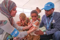 シリア北東部の品難民キャンプで、子どもたちの栄養状態をチェックするユニセフの保健員(2017年6月10日撮影)